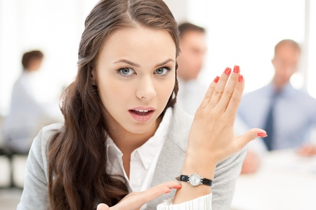 oclock: business and time management concept - businesswoman pointing at her watch