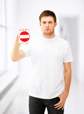 blank road sign: picture of young man showing no entry sign Stock Photo