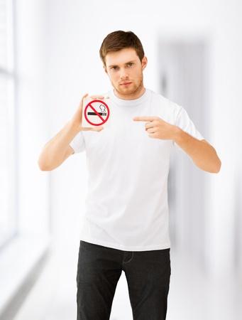 joven fumando: Imagen del hombre joven apuntando a señal de no fumar