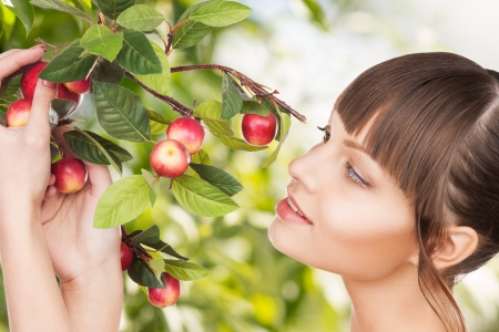eco, bio and organic concept - beautiful woman with apple twig Stock Photo - 21136476