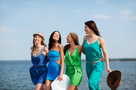 summer holidays and vacation - girls walking on the beach photo