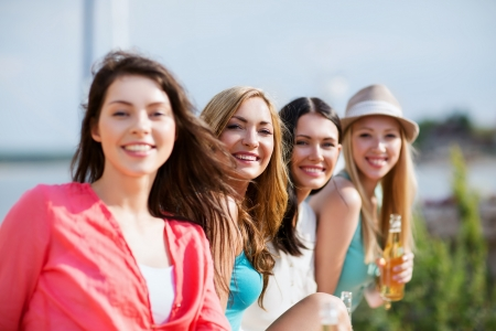 non alcoholic beer: summer holidays and vacation - girls with drinks on the beach Stock Photo