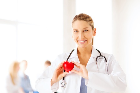 healthcare and medical concept - female doctor with heart photo