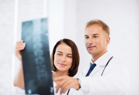 healthcare, medical and radiology concept - two doctors looking at x-ray photo
