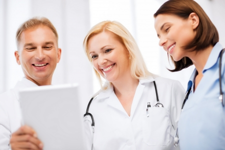 healthcare and technology concept - doctors looking at tablet pc