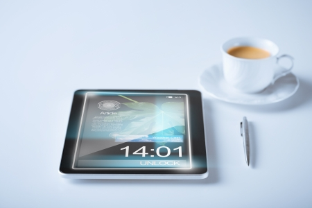 business and technology concept - tablet pc and cup of coffee photo