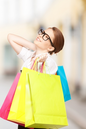 shopping and tourism concept - beautiful woman with shopping bags in ctiy Stock Photo - 21136567