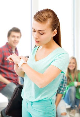 education and time management concept - student girl looking at wristwatch photo