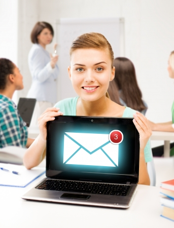 education, communication and internet concept - girl holding laptop with email sign at school photo