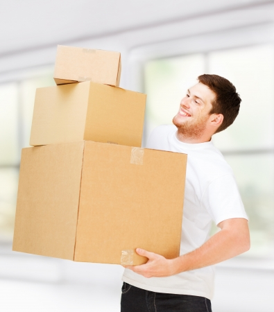 accomodation: new home and post delivery concept - young man carrying carton boxes Stock Photo