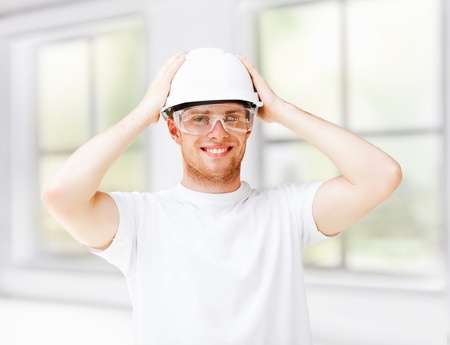 architecture concept - male architect in helmet with safety glasses photo