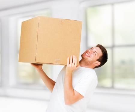 man carrying box: new home and post delivery concept - man carrying carton heavy box Stock Photo