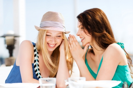 summer holidays and vacation - girls gossiping in cafe on the beach Stock Photo