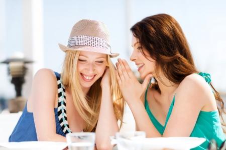 riendo: vacaciones de verano y vacaciones - muchachas de cotilleo en la cafeter�a en la playa
