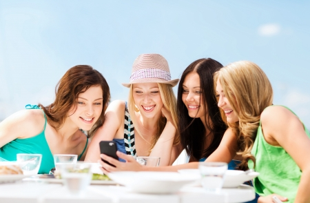 taking video: summer holidays, vacation and technology - girls looking at smartphone in cafe on the beach