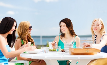 summer holidays and vacation - girls in cafe on the beach photo
