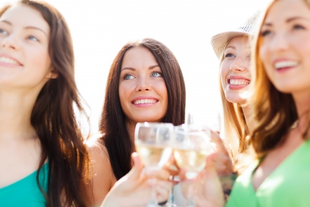 friends drinking: summer holidays, vacation and celebration - girls with champagne glasses