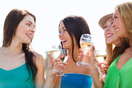 toasting wine: summer holidays, vacation and celebration - girls with champagne glasses