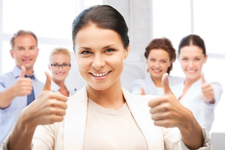 business and success - happy businesswoman showing thumbs up in office