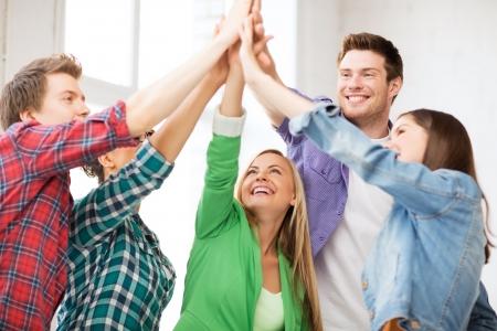 onderwijs en vriendschap concept - gelukkige studenten die hoogte vijf op school Stockfoto