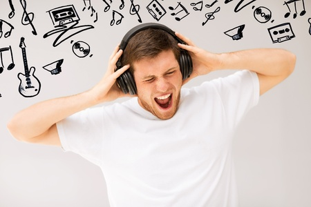 la música y la tecnología - hombre joven con los auriculares escuchando música a todo volumen