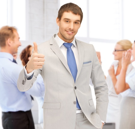 business and success - happy businessman showing thumbs up in office photo