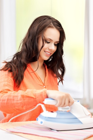 home and housework concept - perfect housewife ironing clothes. photo