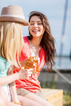 nonalcoholic beer: summer holidays and vacation - girls with drinks on the beach Stock Photo