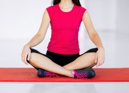 sport and yoga concept - girl sitting in lotus position and meditating photo