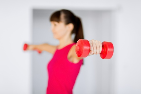sport and recreation concept - sporty woman hands with light red dumbbells photo