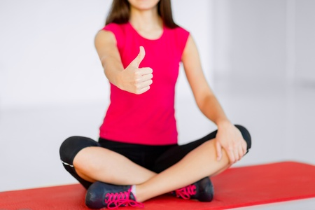 sport and yoga concept - girl sitting in lotus position and showing thumbs up photo