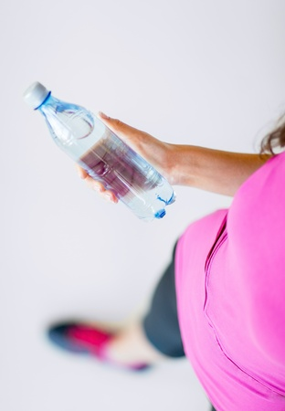 sport and diet concept - sporty woman with bottle of water photo