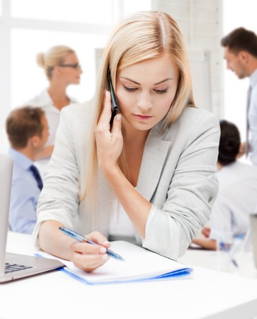 business concept - businesswoman talking on the phone and taking notes in office photo