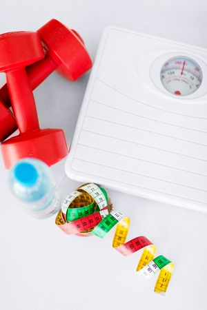 fitness goal: sport and diet concept - scales, dumbbells, bottle of water and measuring tape Stock Photo