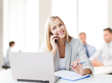 business concept - businesswoman talking on the phone in office photo