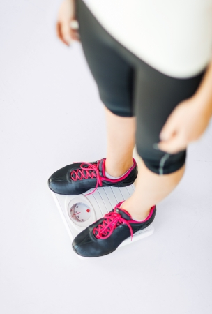 scale weight: sport, diet and weight loss concept - woman legs standing on scales