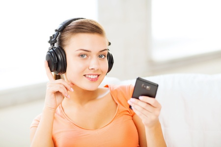 music, internet and shopping - woman with headphones and smartphone at home photo