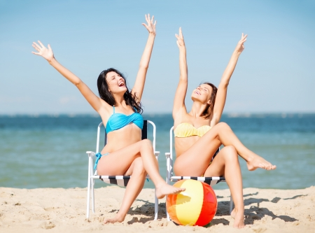 friends party: summer holidays and vacation - girls sunbathing on the beach chairs
