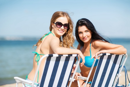 summer holidays and vacation - girls sunbathing on the beach chairs photo