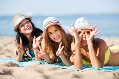 summer holidays and vacation - girls sunbathing on the beach Фото со стока