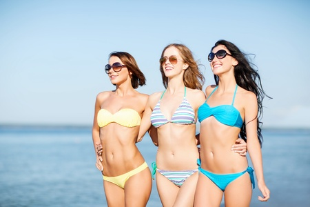 summer holidays and vacation - girls in shades and bikini walking on the beach photo