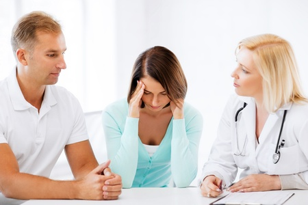 couple talking: healthcare and medical concept - doctor with patients in cabinet