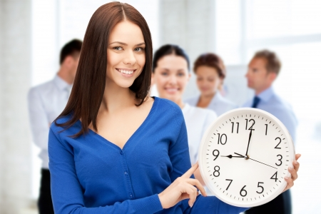 business and time management concept - businesswoman pointing at alarm clock photo