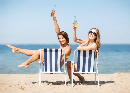 nonalcoholic beer: summer holidays and vacation - girls sunbathing and drinking on the beach chairs