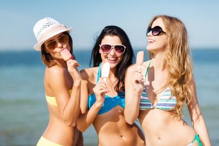 niñas en bikini: vacaciones de verano y vacaciones - chicas en bikini con helado en la playa Foto de archivo