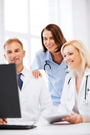 electronical: healthcare, medical and technology - group of doctors looking at computer on meeting