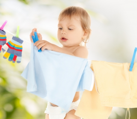 bright picture of adorable baby doing laundry 版權商用圖片