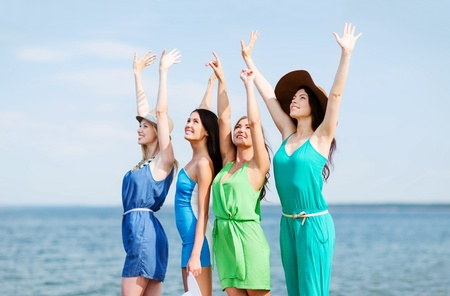 people looking up: summer holidays and vacation - girls with hands up on the beach Stock Photo