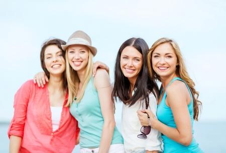 zomervakantie en vakantie - groep meisjes chillen op het strand Stockfoto
