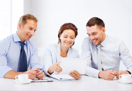 business and technology concept - business team looking at tablet pc in office photo